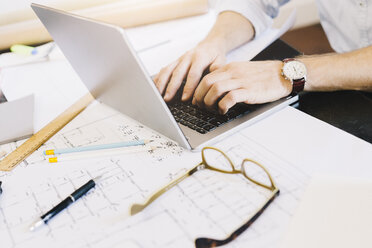 Man using laptop next to construction plan at desk - GIOF03048