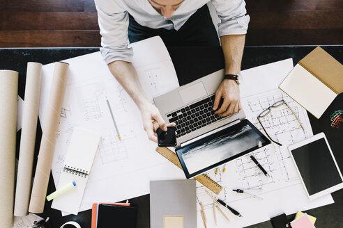 Man using laptop next to construction plan at desk, top view - GIOF03051