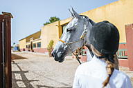 Portrait of horse with back view of woman wearing riding helmet - KIJF01697