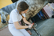 Young woman cleaning hoof of horse - KIJF01700
