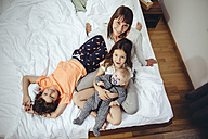 Happy mother in bed with her three children - MFF03696