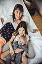 Happy mother in bed with her three children - MFF03699