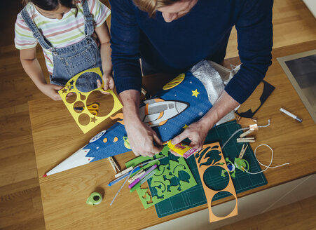 Father and daughter creating her space themed school cone at home - MFF03708