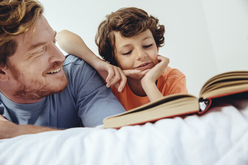 Father and son reading book in bed - MFF03711