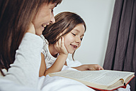 Mother and daughter reading book in bed - MFF03717