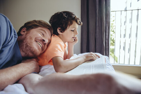 Son reading to his father on bed - MFF03726