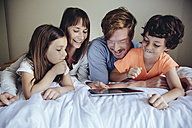 Children and their parents looking at tablet on bed - MFF03729