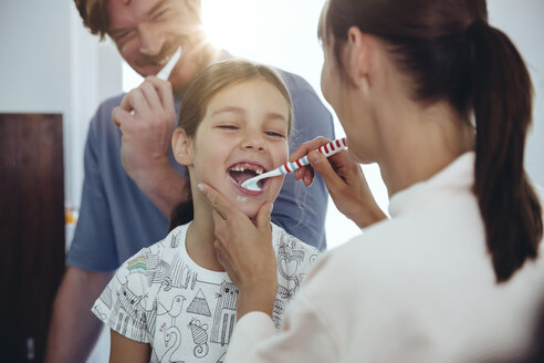 Mother brushing daughter's teeth in bathroom - MFF03732