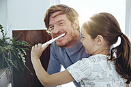 Daughter brushing her father's teeth in bathroom - MFF03735