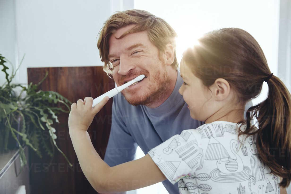 Daughter brushing her father's teeth in bathroom - MFF03735 - Mareen Fischinger/Westend61