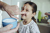 Father putting facial cream on daughter's face - MFF03744