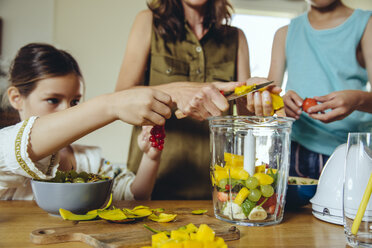 Mother and children putting fruit into a smoothie blender - MFF03753