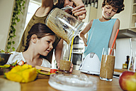 Mother with two children pouring a smoothie into glasses - MFF03759