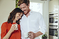 Happy couple in kitchen holding coffee mugs - MFF03771