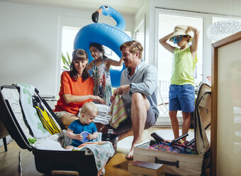 Happy family of five packing for holiday trip - MFF03774