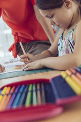 Mother helping girl doing her schoolwork at home - MFF03786