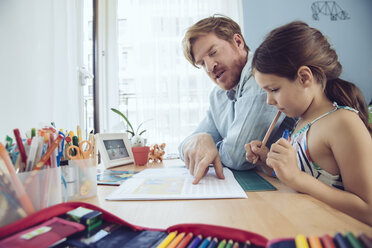 Father helping girl doing her schoolwork at home - MFF03789