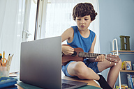Boy using laptop to play a song on an ukulele - MFF03792