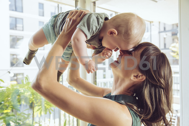 Mother lifting up her baby at home - MFF03813