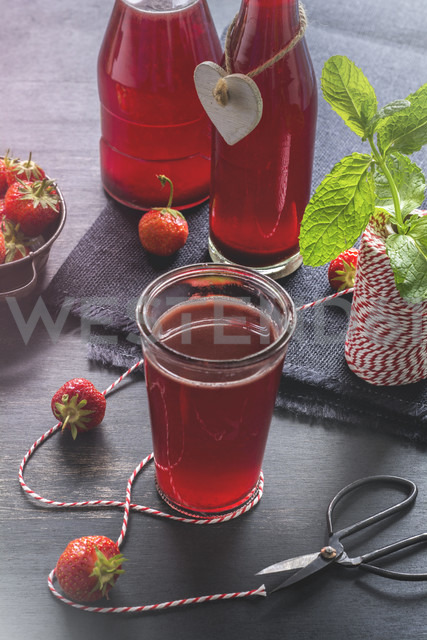 Glass and glass bottles of homemade strawberry lemonade - ODF01532