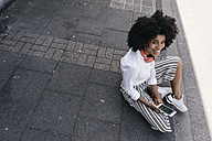 Smiling young woman sitting on pavement - KNSF02252