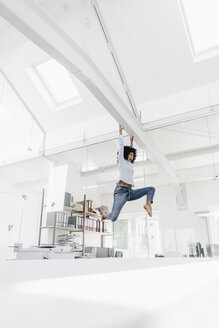 Excited young woman hanging on beam in office - KNSF02261