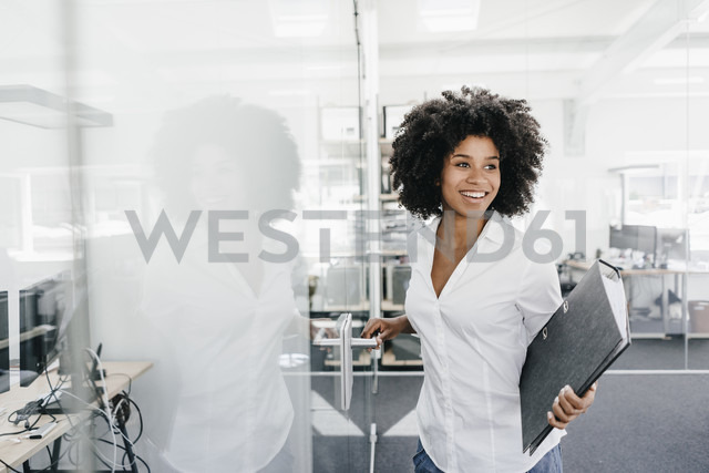 Smiling young woman in office holding file folder - KNSF02273 - Kniel Synnatzschke/Westend61