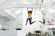 Young woman hanging on beam in office - KNSF02285