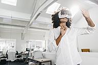 Woman wearing VR glasses in office - KNSF02306