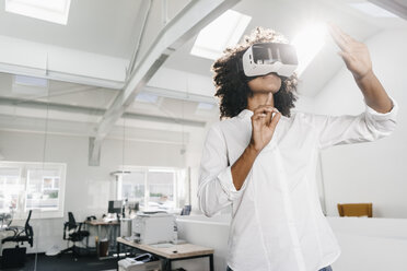 Woman wearing VR glasses in office - KNSF02306