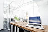 Laptop on wooden table in office - KNSF02318