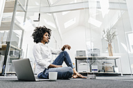 Young woman sitting on floor in office with laptop - KNSF02327