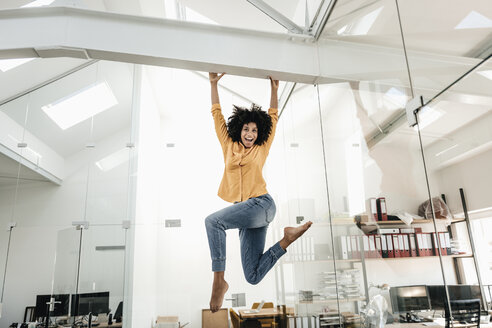 Happy young woman hanging on beam in office - KNSF02354