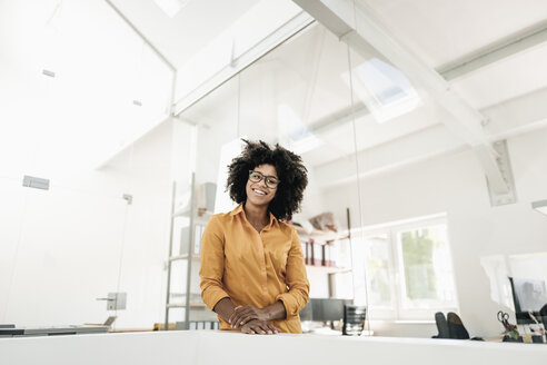 Portrait of young woman with glasses in office - KNSF02357
