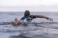 Back view of man on surfboard - KNTF00869