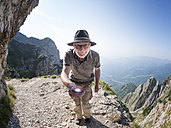 Italy, Veneto, Strada delle 52 Gallerie, hiker holding torch - LAF01856
