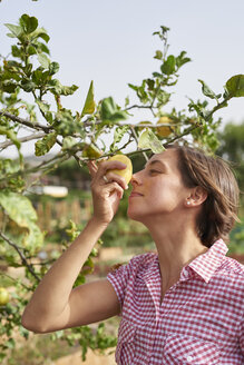 Young woman smelling a lemon - PACF00053