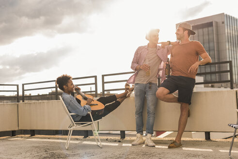 Three friends having a rooftop party - UUF11456