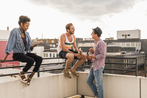 Three friends socializing on a rooftop party - UUF11474