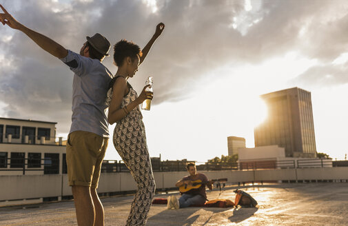 Young couple dancing on a rooftop party - UUF11483