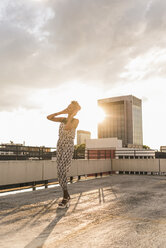 Happy young woman with headphones on rooftop - UUF11486