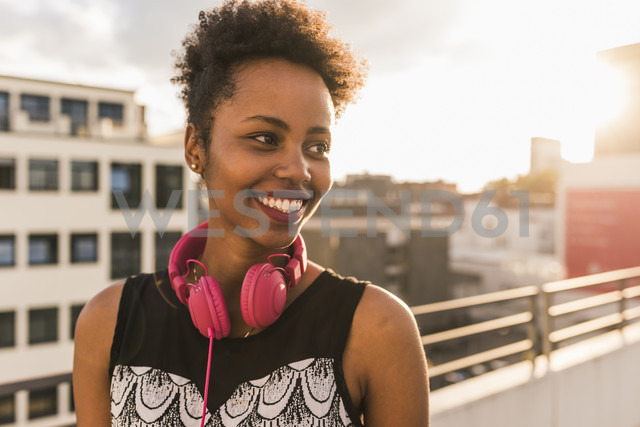 Portrait of happy young woman with headphones on rooftop - UUF11492