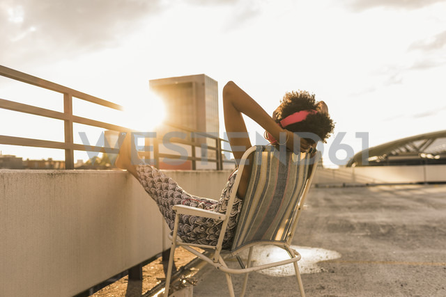 Young woman with headphones sitting on rooftop - UUF11504 - Uwe Umstätter/Westend61