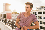 Young man with beer bottle on rooftop at sunset - UUF11507
