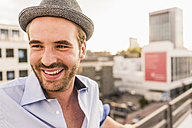 Portrait of happy young man on rooftop - UUF11510