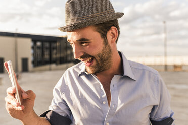 Happy young man with cell phone on rooftop - UUF11513