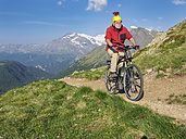 Italy Lombardy, Passo di Val Viola, Man riding e-bike in the mountains with action cam on his helmet - LAF01858