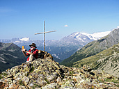 Italy Lombardy, Passo di Val Viola, Man taking pictures with his smartphone, sitting at summit cross - LAF01861
