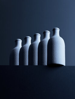 Row of five bottles in front of dark background, 3D-Rendering - DRBF00021