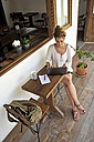 Young woman sitting on veranda of a coffee shop using laptop - ECPF00049